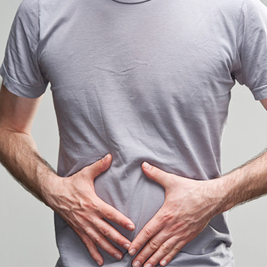 Man holding stomach, Improve digestion with Chiropractic Care Cloverfield
